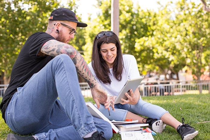 Two people studying together in a park, using tablets and books