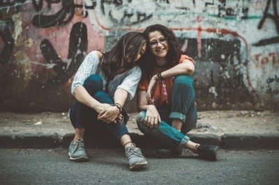 Two friends leaning together on pavement