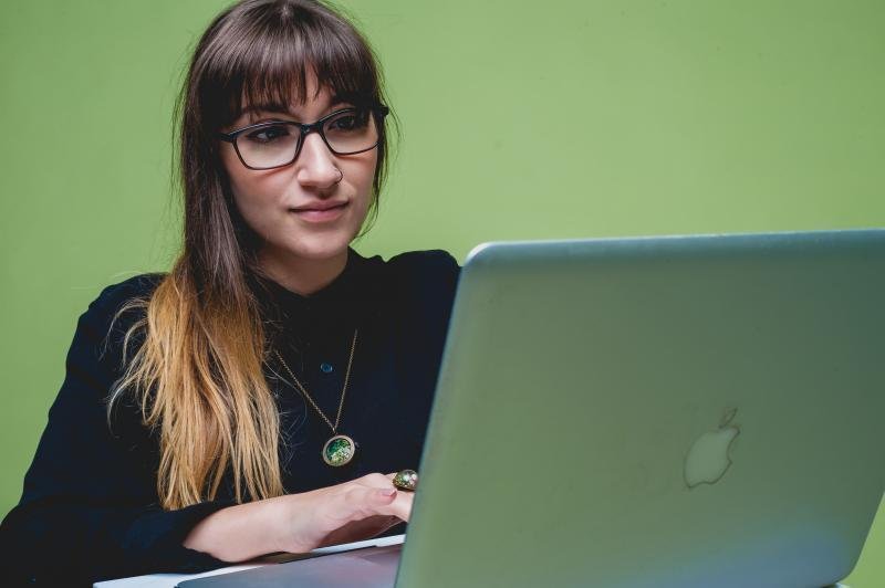 Young person in glasses and black sweater studies at macbook